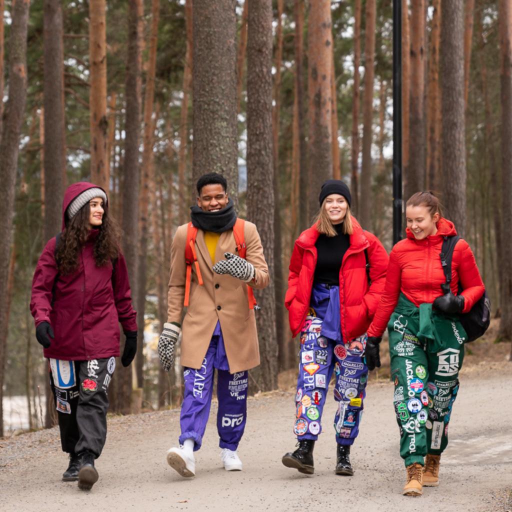 Opiskelijoita kävelemässä metsätiellä.