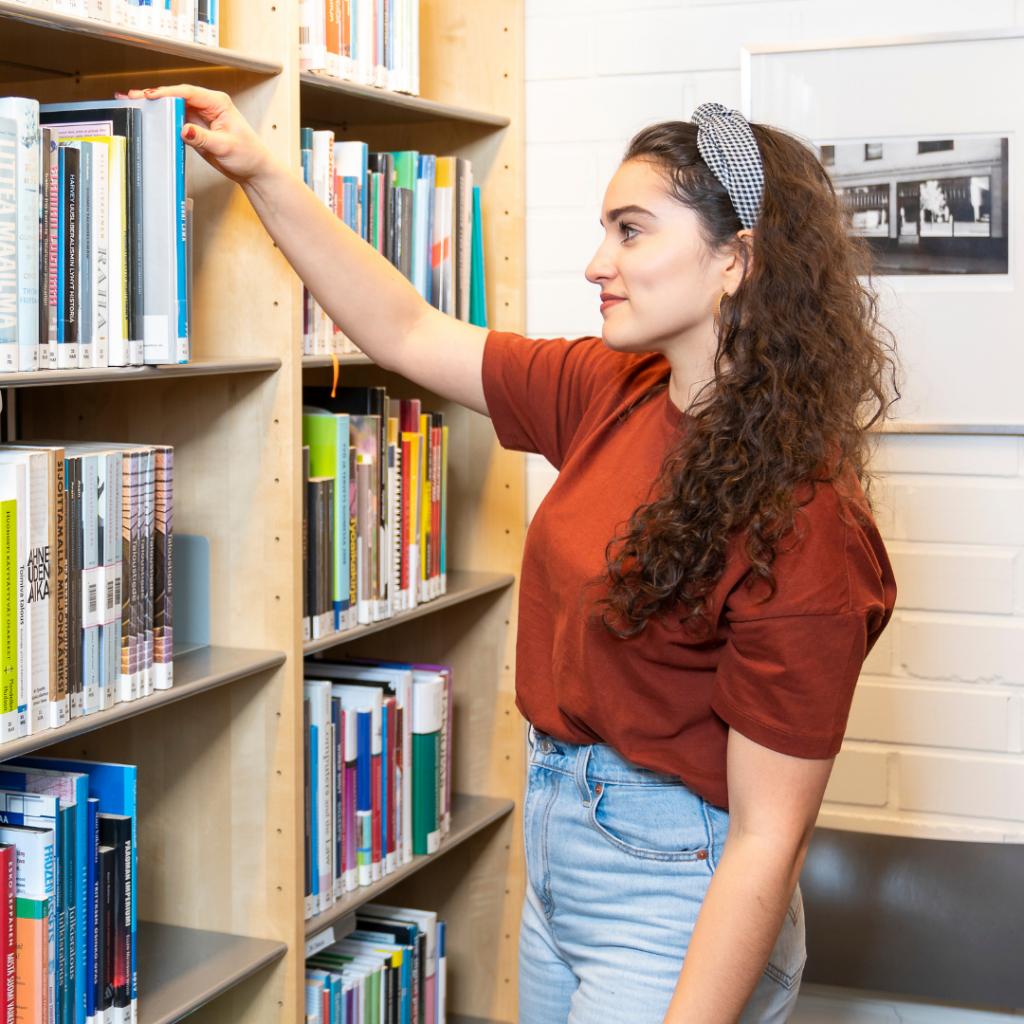 Opiskelijatyttö kirjahyllyn edessä.